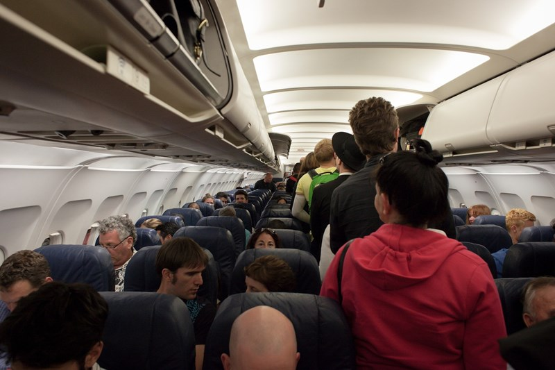 passengers walking down aisle while boarding an airplane